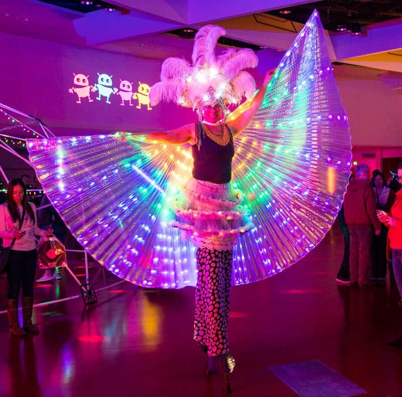 A stilt walker with a cape made from colorful LEDs spreads the cape and poses