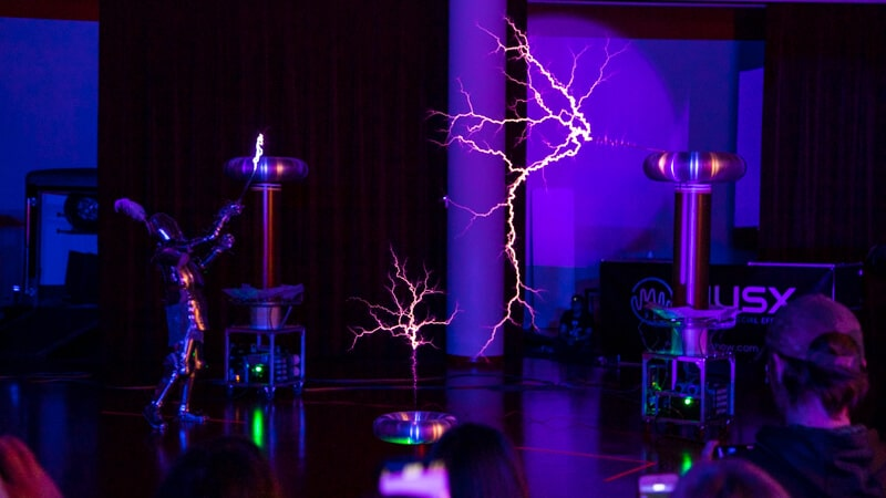 Tesla Coils emitting lightning while a person in a Knight Faraday Suit plays with the lighting
